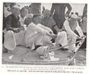 The solemn moment  before the ashes were poured into the water at sangam, Allahabad. Ramdas Gandhi is holding the brass urn. With him are Devadas Gandhi, Pandit Nehru and others.